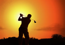 Golfers silhouette. While tee off in a golf course early in the morning Stock Photo