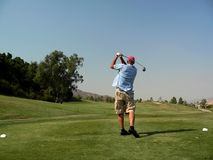 Golfer's Tee Shot. A golfer tees off with a big drive out over the fairway (resubmit - trademarks now removed Stock Photos