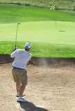Golfer in the sand bunker. Young male golfer hitting the ball from the sand bunker on a beautiful summer day Royalty Free Stock Photo