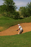 Golfer in the sand bunker. Golfer hitting the ball out of the sand bunker. Sand and golf club are in motion Royalty Free Stock Image