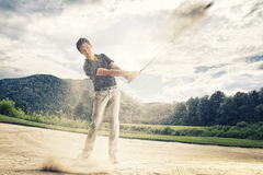 Golfer in sand trap. Male golf player in blue shirt and grey pants hitting golf ball out of a sand trap with sand wedge and sand caught in motion Royalty Free Stock Photos