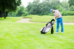 Golfer selecting appropriate club Royalty Free Stock Photos
