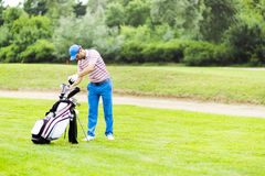 Golfer selecting appropriate club Royalty Free Stock Image