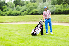 Golfer selecting appropriate club Stock Photo