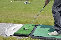 A golfer sets up his shot at a driving, practice range royalty free stock images