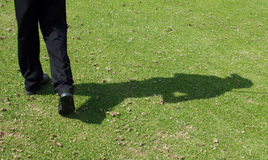 Golfer shadow. Golfer's shadow after completion of swing stock image