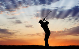 Golfer Silhouette. Silhouette of golfer mid-swing with a beautiful sunset Stock Photo