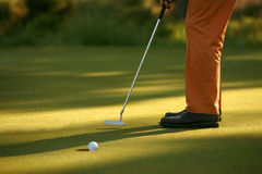 Golfer sinking a putt. Tight shot of a golf ball about to drop in hole after the putt Stock Photo