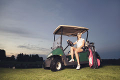 Golfer sitting in golf cart at twilight. Stock Image