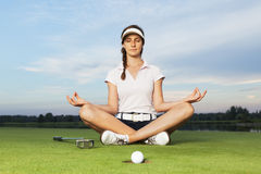 Golfer sitting in yoga posture on golf course. Woman golf player sitting on green in yoga posture focusing on ball dropping into cup Royalty Free Stock Photography