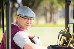 Golfer smiling and posing. In his golf buggy Stock Image
