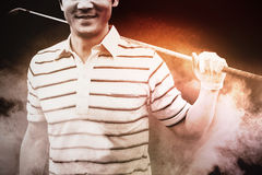 Composite image of golfer standing and holding his club smiling at camera. Golfer standing and holding his club smiling at camera against close up of old table Stock Image