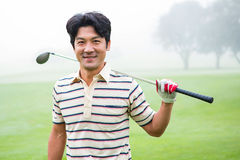 Golfer standing and holding his club smiling at camera. At the golf course Stock Photos
