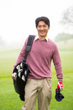 Golfer standing holding his golf bag smiling at camera Royalty Free Stock Images