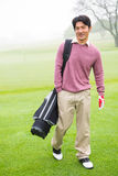 Golfer standing holding his golf bag smiling at camera Royalty Free Stock Image