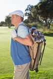 Golfer standing holding his golf bag Stock Image