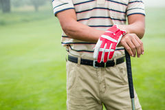 Golfer standing and leaning on his club Stock Photo