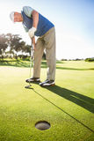 Golfer standing on the putting green watching hole Royalty Free Stock Photos