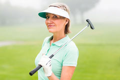 Golfer standing and swinging her club smiling at camera Royalty Free Stock Photos