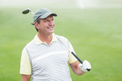 Golfer standing and swinging his club smiling at camera. On a foggy day at the golf course Stock Photo