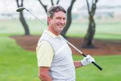 Golfer standing and swinging his club smiling at camera. On a foggy day at the golf course Royalty Free Stock Photo