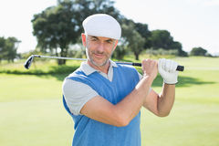 Golfer standing and swinging his club smiling at camera. On a sunny day at the golf course Stock Photography