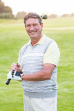 Golfer standing and swinging his club smiling at camera. On a sunny day at the golf course Stock Photos