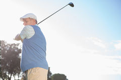 Golfer standing and swinging his club. On a sunny day at the golf course Royalty Free Stock Photo