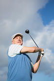 Golfer standing and swinging his club. On a sunny day at the golf course Stock Photos