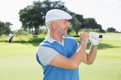 Golfer standing and swinging his club. On a sunny day at the golf course Royalty Free Stock Images