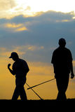 Golfer striking. In the sunset Royalty Free Stock Image