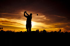 Golfer at Sunset. A golfer silhouetted in the sunset following through his swing royalty free stock images