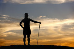 Golfer at sunset looks at view. Stock Image