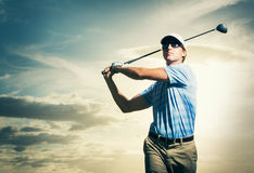 Golfer at sunset. Man swinging golf club with dramatic sunset sky Stock Images