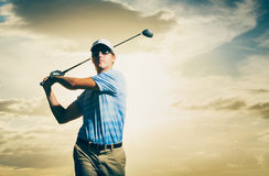 Golfer at sunset. Man swinging golf club with dramatic sunset sky Stock Photos