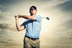 Golfer at sunset. Man swinging golf club with dramatic sunset sky Royalty Free Stock Photos
