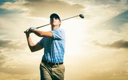 Golfer at sunset. Man swinging golf club with dramatic sunset sky Royalty Free Stock Photo