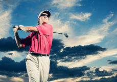 Golfer at sunset. Man swinging golf club with dramatic sunset sky backdrop Royalty Free Stock Image
