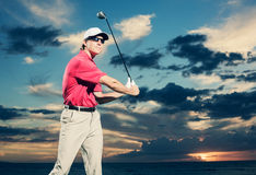 Golfer at sunset Royalty Free Stock Images