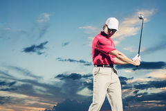 Golfer at sunset. Man swinging golf club with dramatic sunset sky backdrop Stock Photography