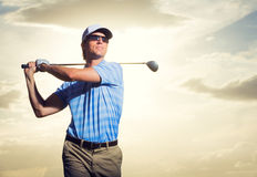 Golfer at sunset. Man swinging golf club with dramatic sunset sky backdrop Stock Photos