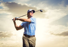 Golfer at sunset. Man swinging golf club with dramatic sunset sky backdrop Royalty Free Stock Photo