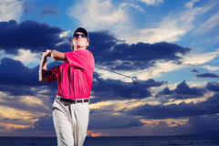 Golfer at sunset. Man swinging golf club with dramatic sunset sky backdrop Stock Image