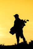 Golfer at sunset. On the orange sky Stock Image