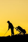 Golfer at sunset. On the orange sky Royalty Free Stock Photography