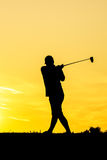 Golfer at sunset. On the orange sky Royalty Free Stock Photo