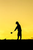 Golfer at sunset. On the orange sky Stock Images