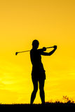 Golfer at sunset. On the orange sky Royalty Free Stock Image