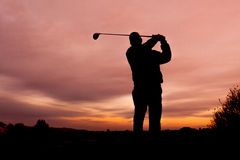 Golfer at Sunset Teeing Off Stock Photography