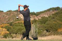 Golfer swing finish. Athletic male golfer finishing swing stock photo